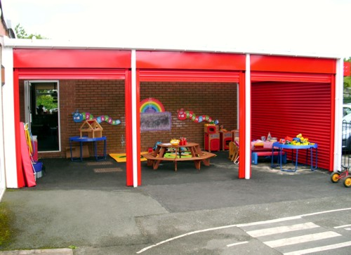 The Coniston Wall Mounted Canopy with Secure Roller Shutters Installed at Middlewich Primary School in Cheshire - Perfect for Winter Outdoor Play